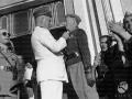 Mussolini appunta un onorificenza sulla camicia nera di un mutilato davanti al portale d ingresso della Casa del Mutilato di Trapani