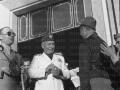 Mussolini ripreso sorridente tra un invalido e un mutilato in camicia nera davanti al portale d ingresso della Casa del Mutilato di Trapani